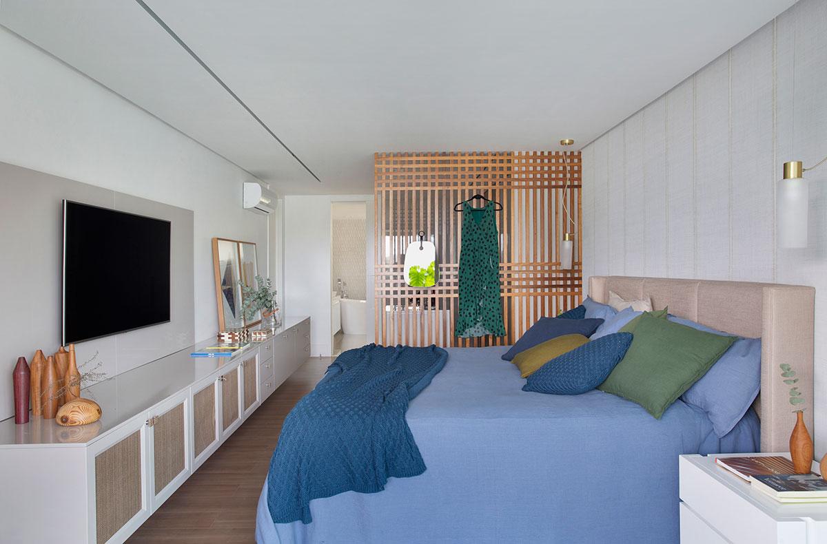 Quarto com decoração clean.  Cama grande com tecidos azuis, biombo de madeira, televisão na parede e um armário que se estende por toda a parede.
