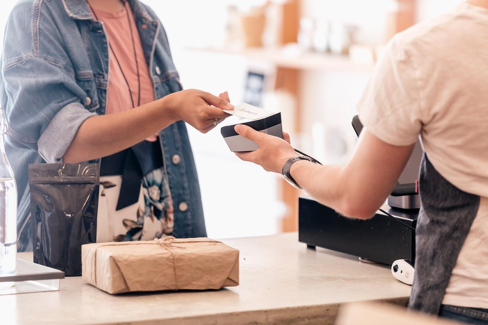 Uma pessoa entregando um cartão para outra pessoa em um estabelecimento.