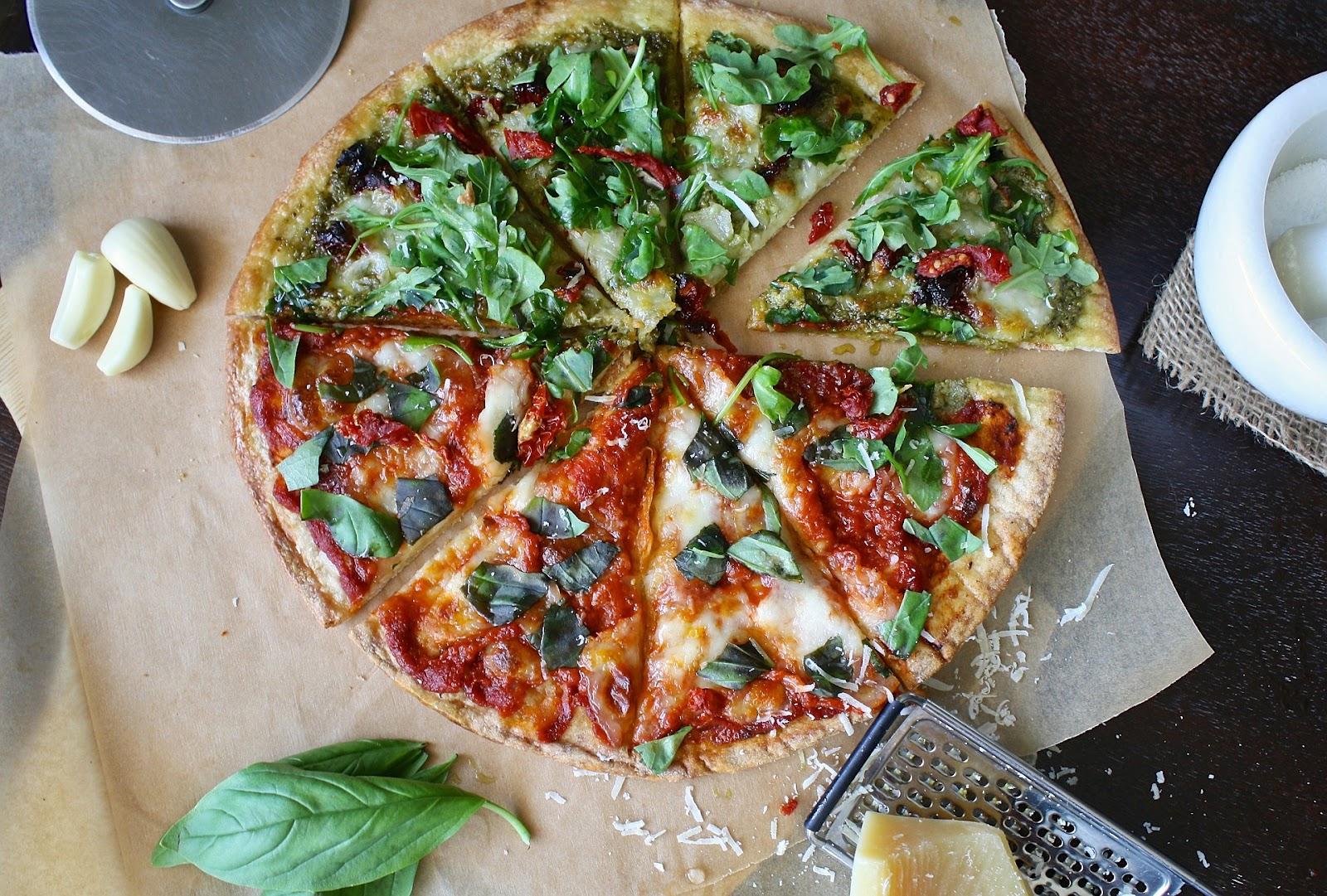 פיצה מחולקת עם רוטב אדום ובזיליקום