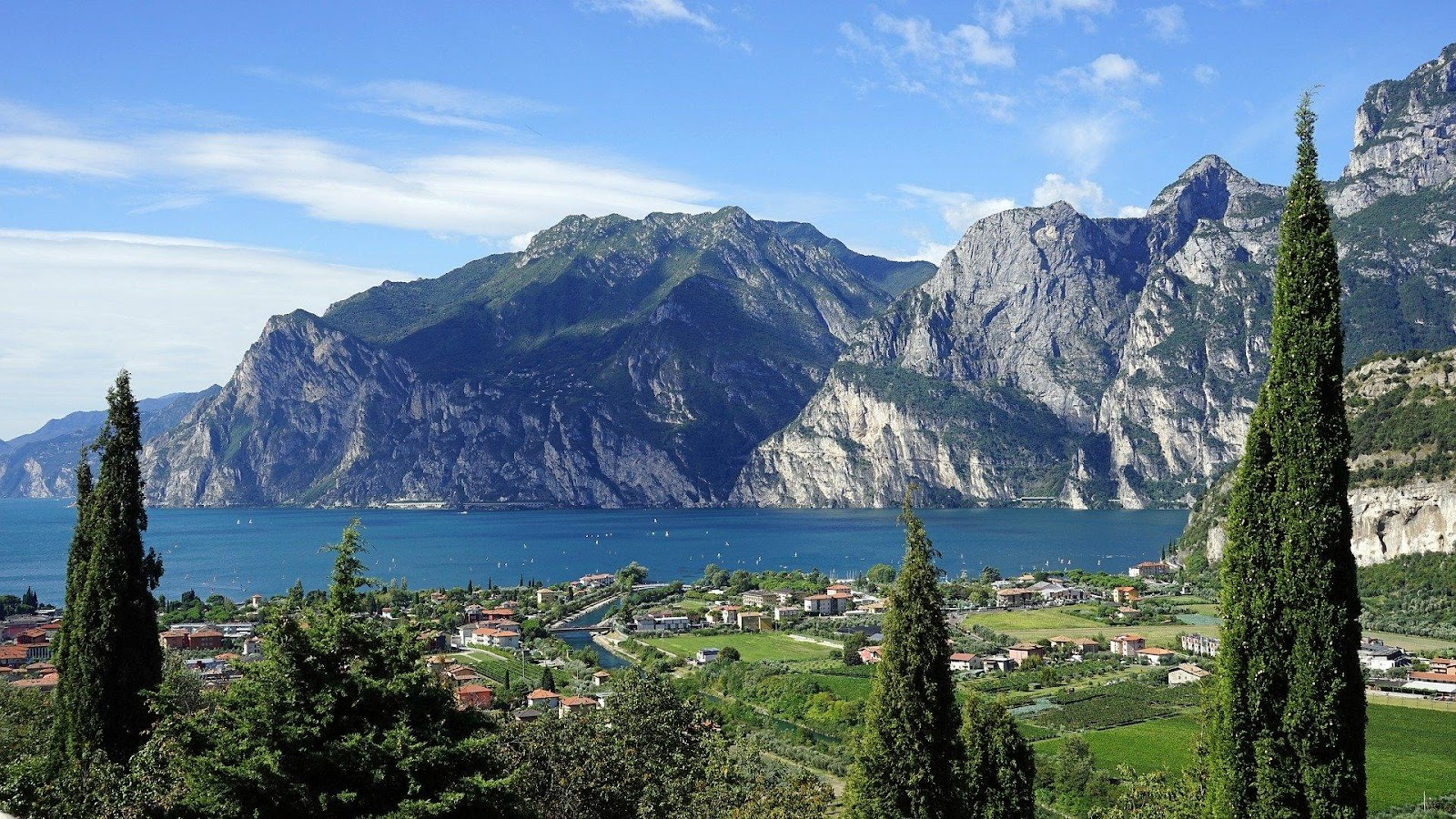 lago di garda crystal clear blue lake in italy surrounded by cliff mountains and green fields