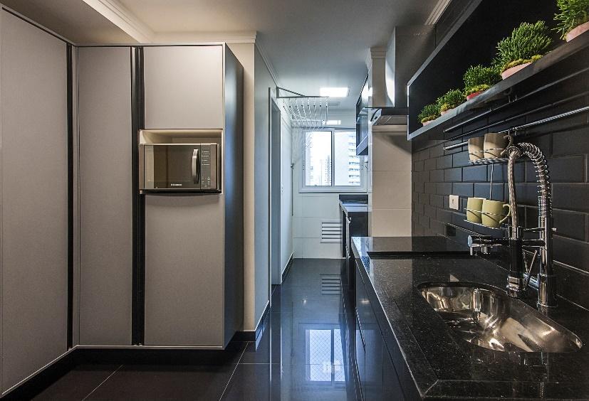 Cozinha em estilo moderno, com azulejo do metro preto fosco, bancada de mármore preta e piso porcelanato preto com armários preto e branco.