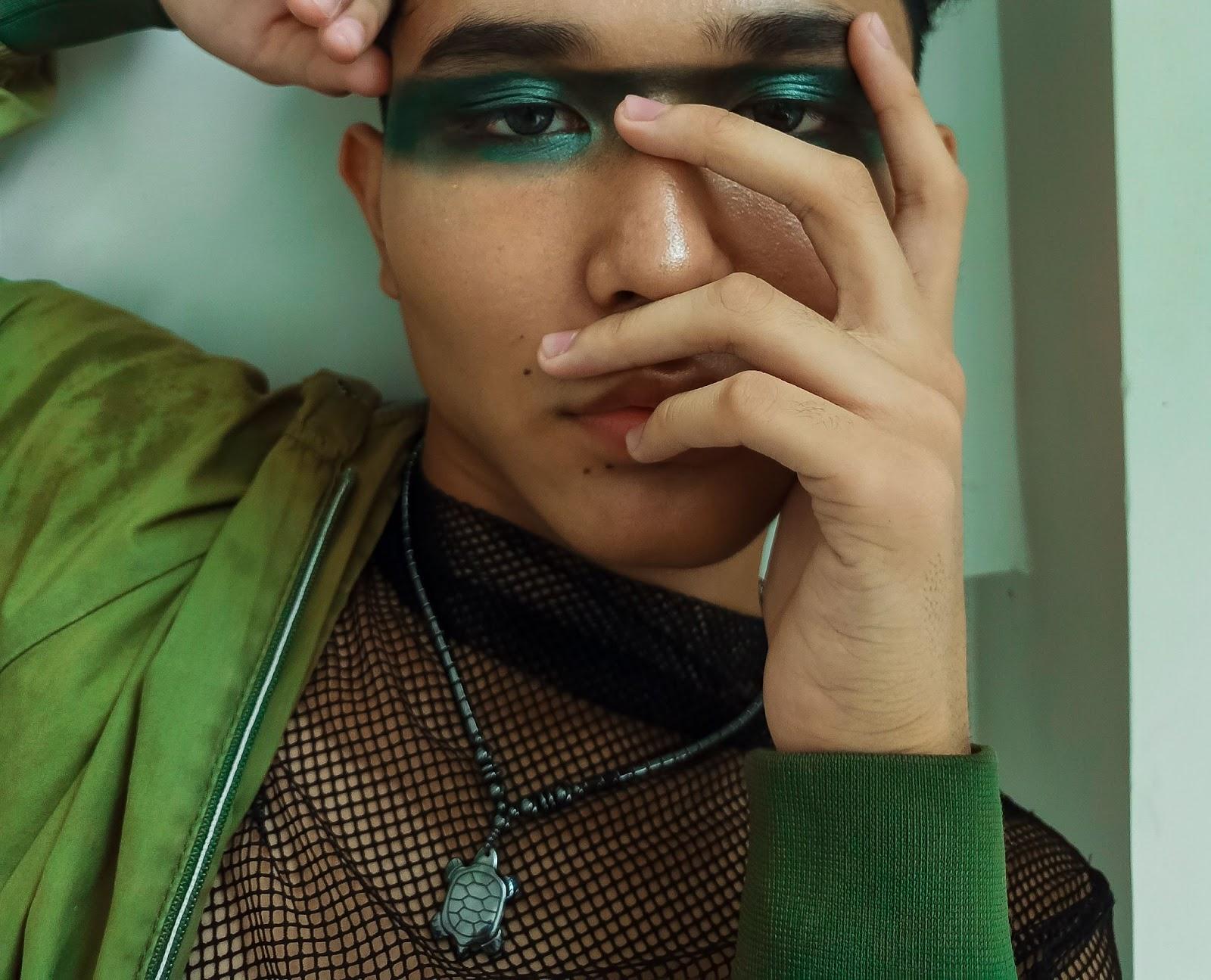 Foto de um homem com a mão no rosto e maquiagem verde nos olhos