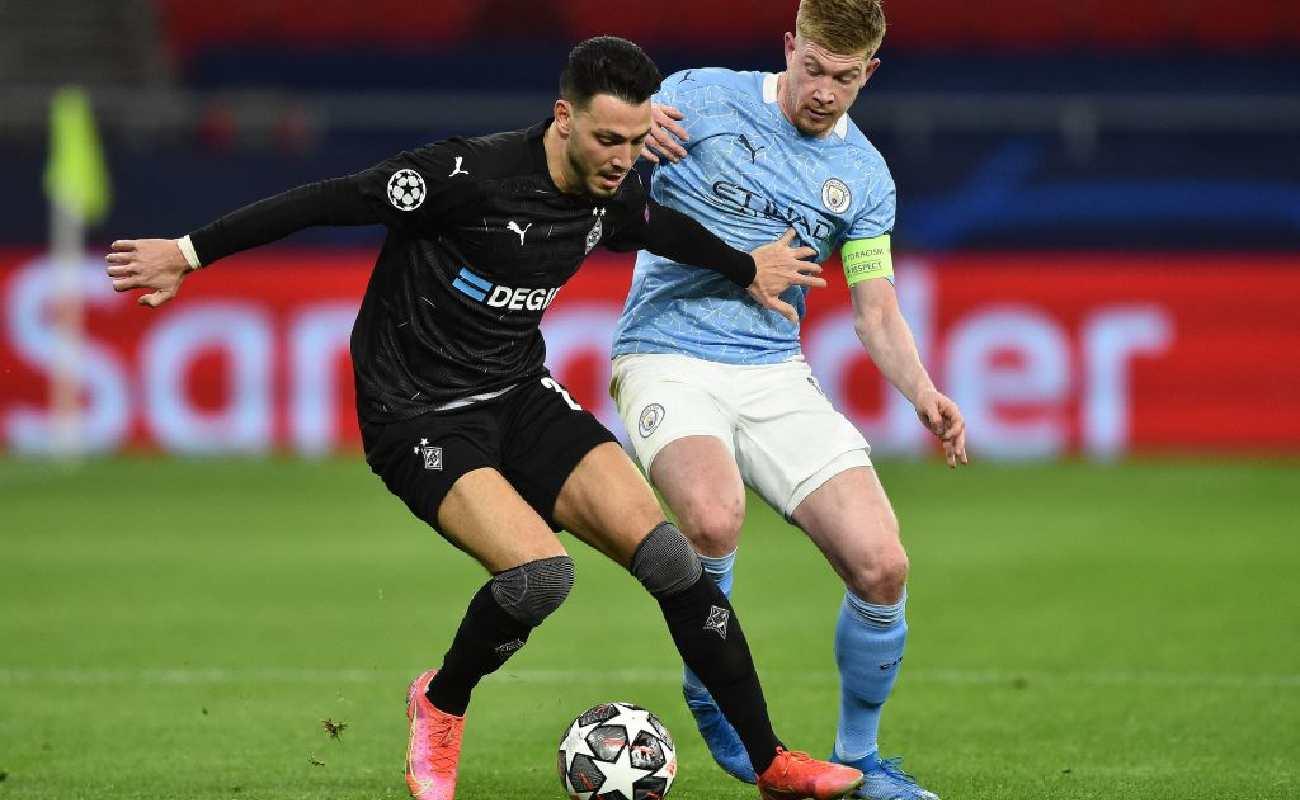 Alt: Kevin de Bruyne battles with midfielder Rami Bensebaini - Photo by Attila KISBENEDEK / AFP) (Photo by ATTILA KISBENEDEK/AFP via Getty Images
