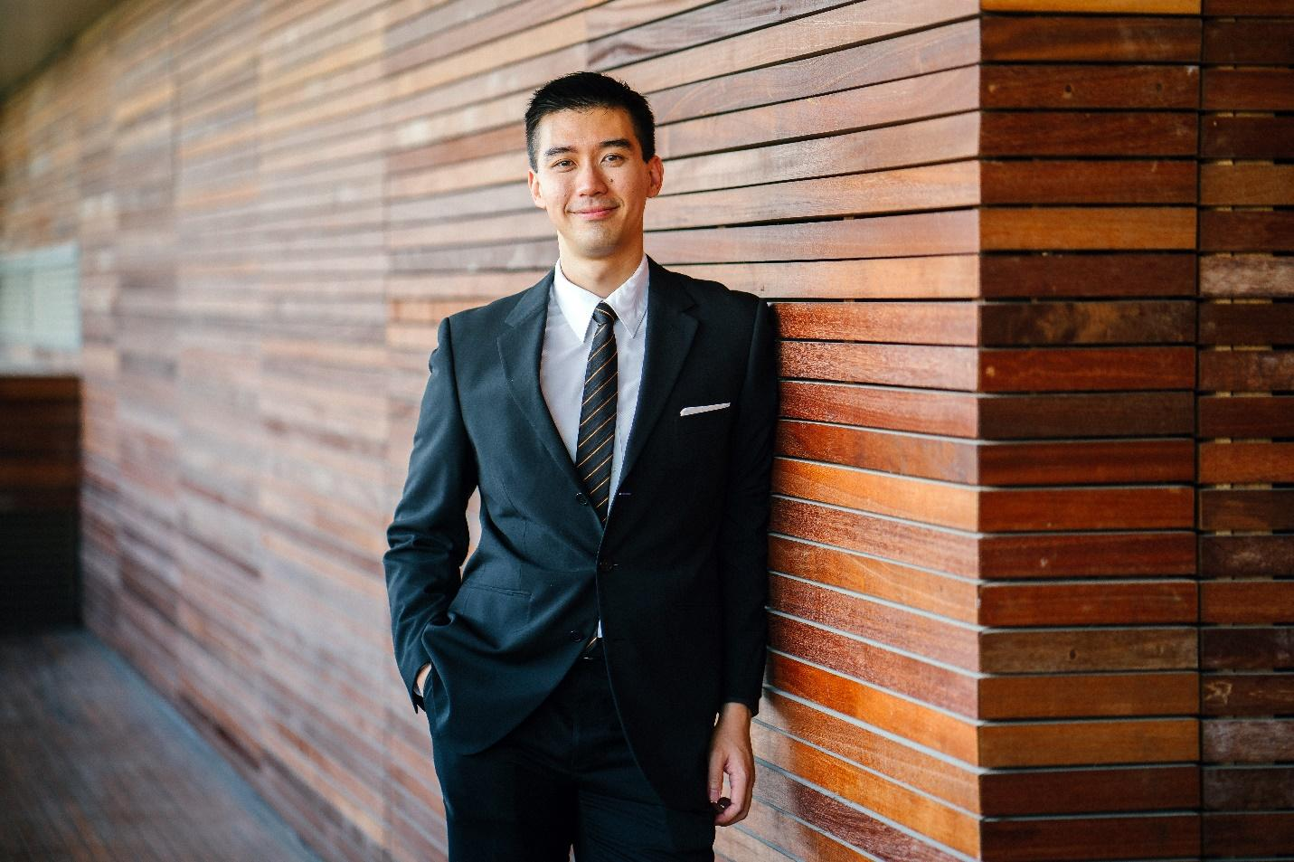 Young professional man smiling at the camera and wearing a black suit leaning on brown wood wall