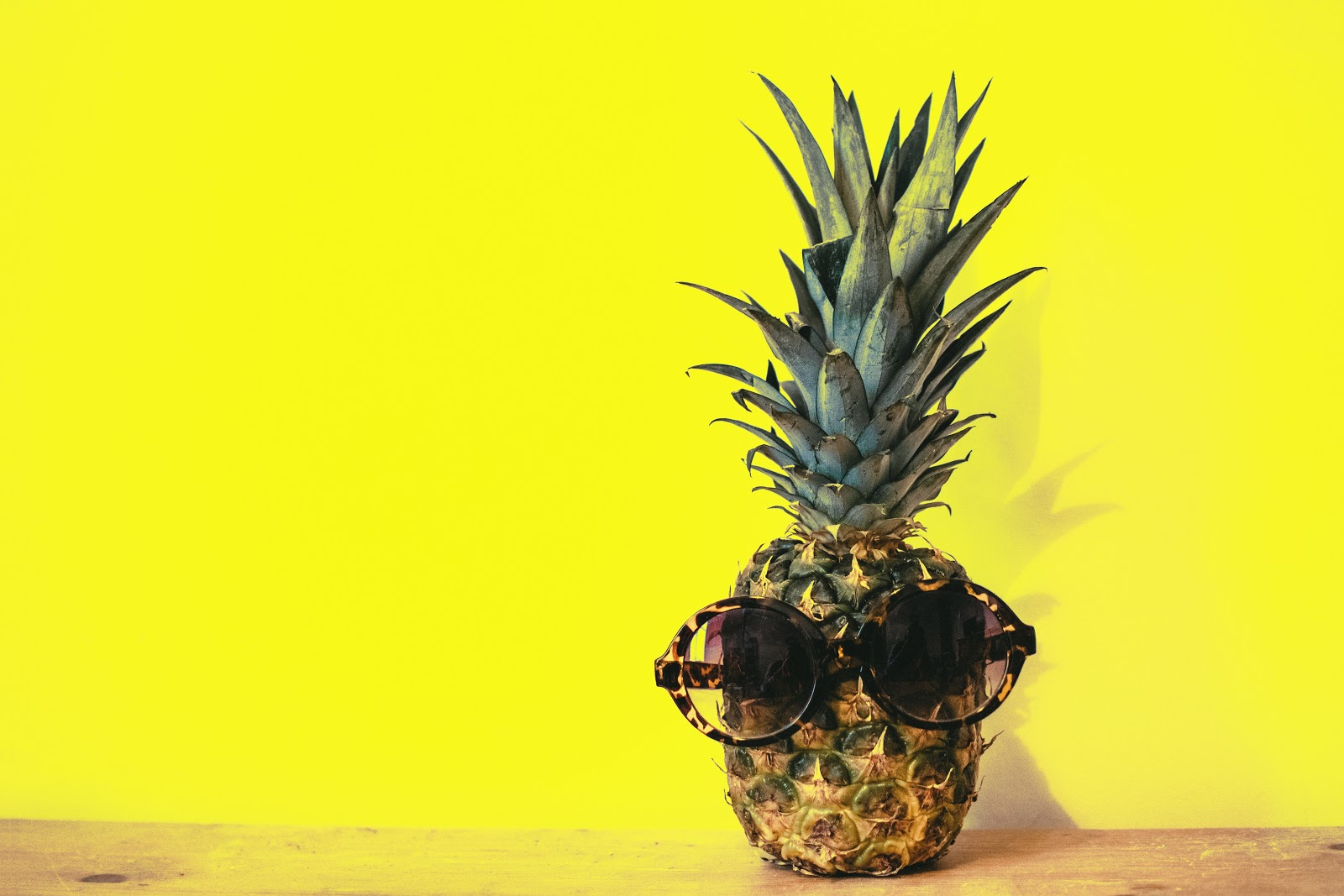 pineapple wearing sunglasses in front of a yellow background