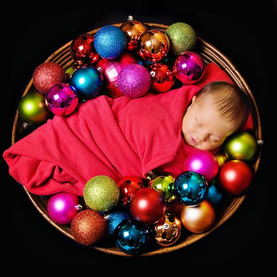 fun christmas card idea of baby bundled in ornaments for holiday card photo