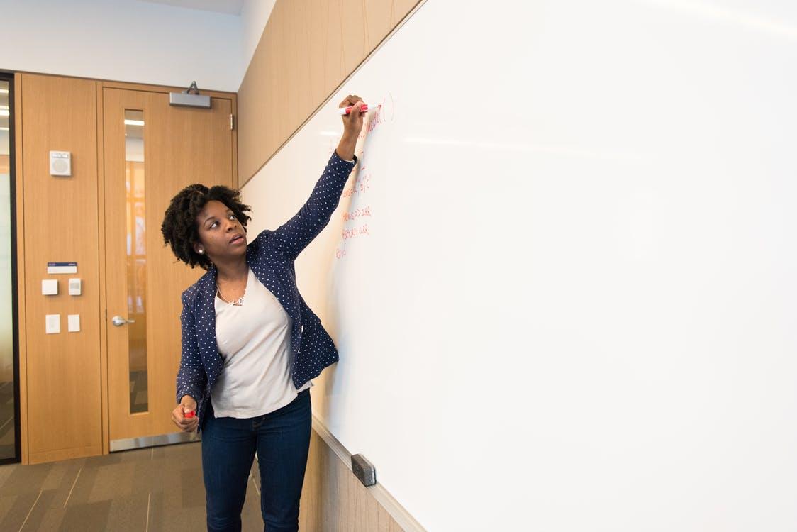 A woman writes on a whiteboard