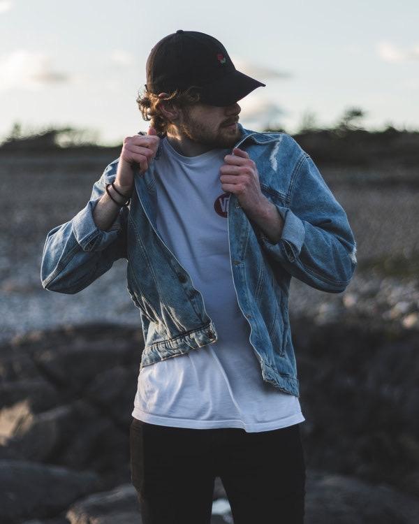 Um homem usando boné com uma jaqueta jeans posando em um campo aberto.