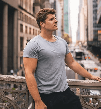 justin woll ecommerce university with the infamous looking to the left pose against a city street with traffic