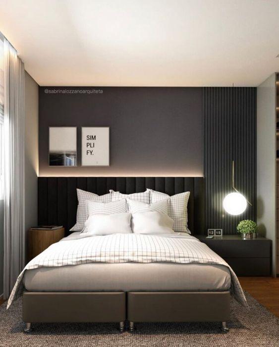 Quarto de casal com parede preta com canto direito revestida de madeira ripada preto, criado mudo preto e cabeceira estofada preta e piso de madeira.