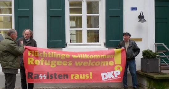 Genossen mit Transparent: »Flüchtlinge willkommen... Rassisten raus! DKP«.