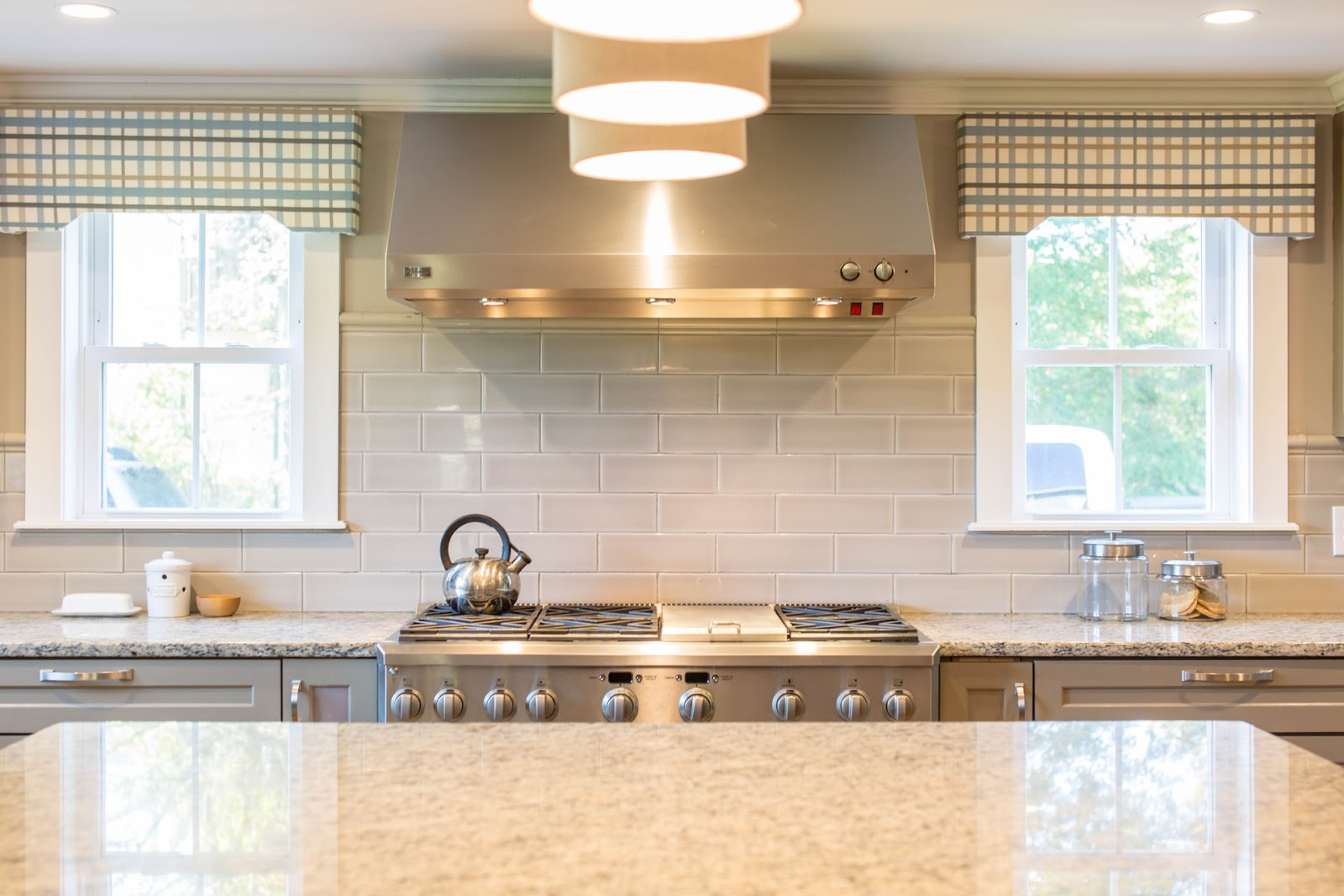 A monochromatic kitchen with statement decor; a light grey and white kitchen with two windows and statement lights