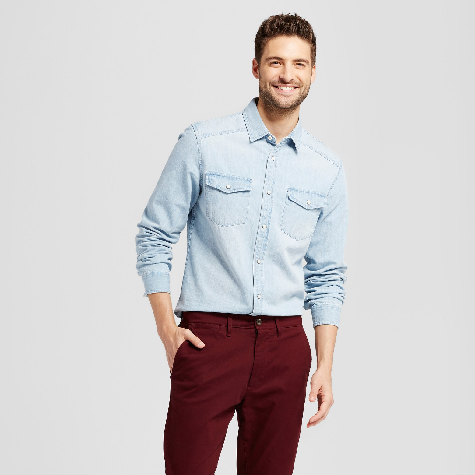 Man wearing long sleeve denim button-up with maroon pants.