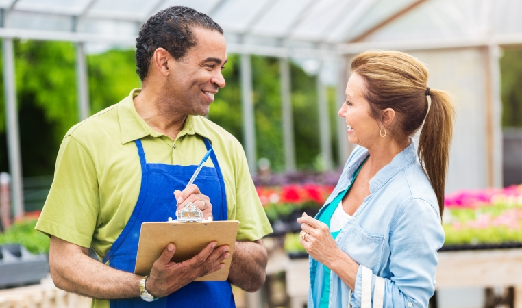 a woman speaking with a clerk at a plant nursery