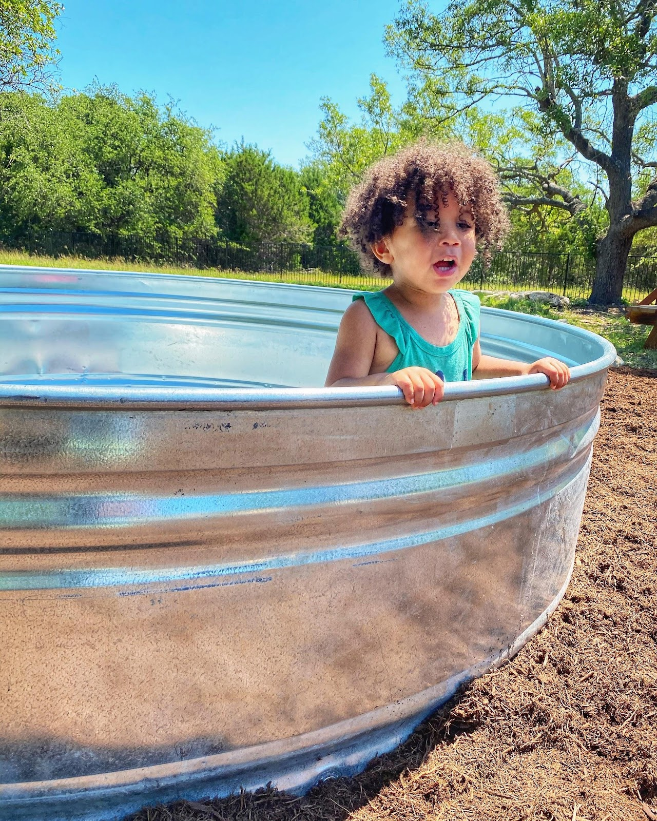 toddler sitting in a stocktank pool