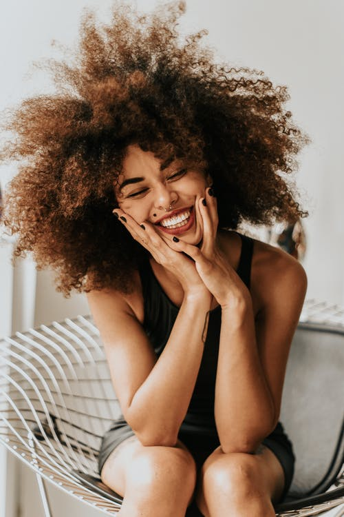 Woman Sitting And Smiling Tips For A Better Smile