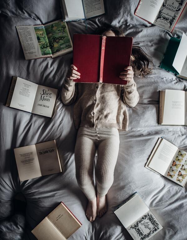 Uma mulher deitada com um livro aberto e vários outros livros abertos ao redor dela. A foto foi tirada de cima.