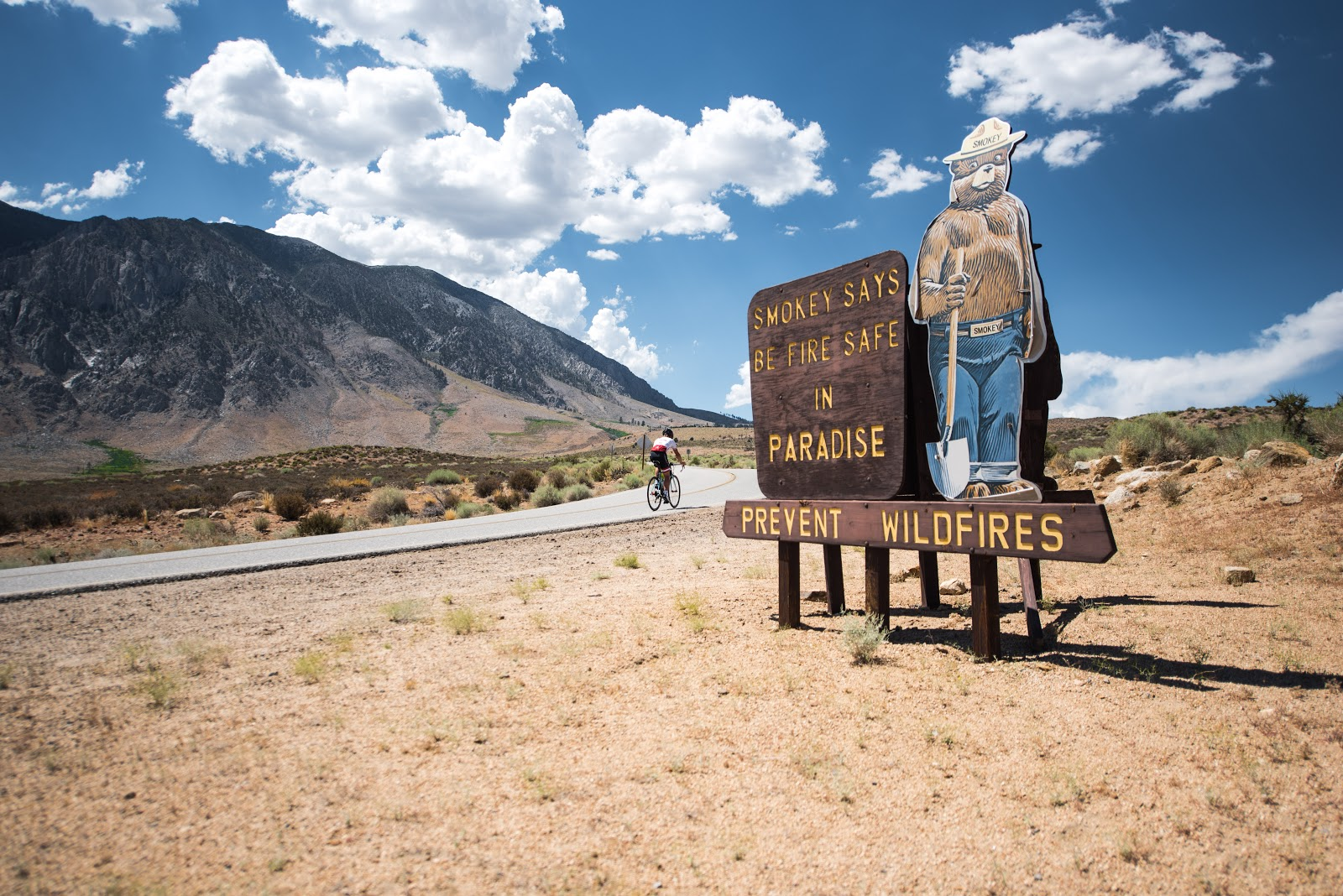 Bicyclist passing Smoky the Bear sign on Rock Creek Road Inyo County