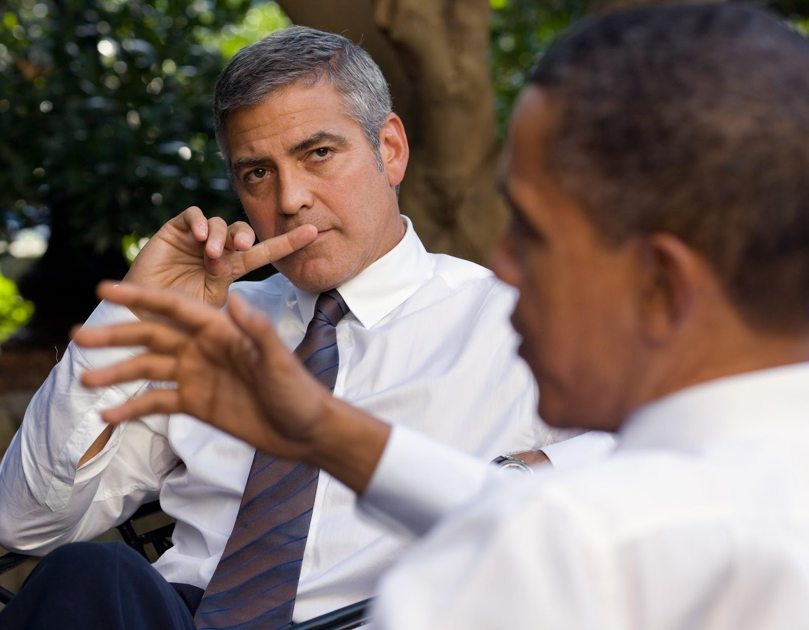 A close-up of George Clooney as he listens to President Barack Obama who is out-of-focus in the bottom of the image. The two are discussing the ethics of using machine learning to aid the Sudanese.