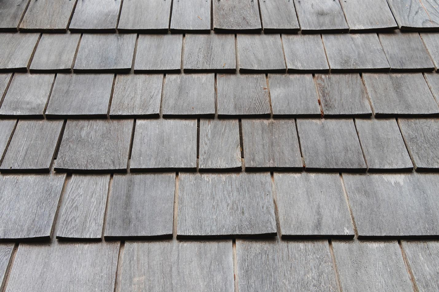 Wooden roof shingles damaged from snow and salt.