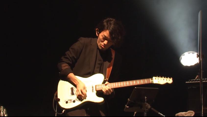 ギターを弾いている男性  自動的に生成された説明