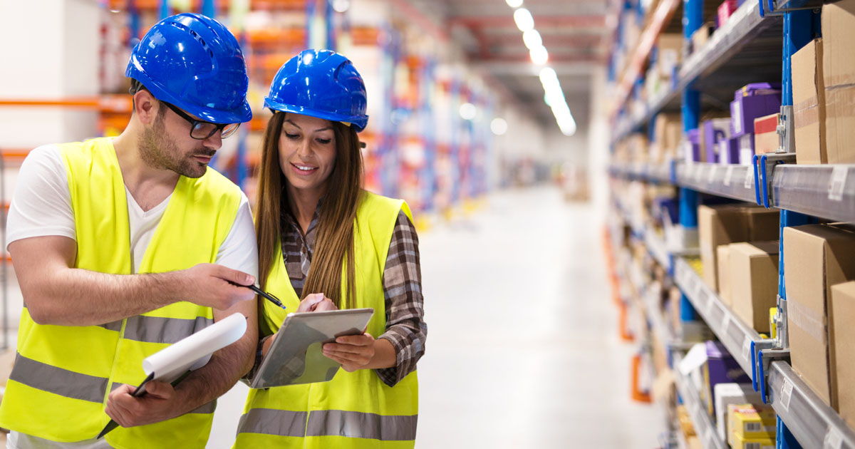 two people in warehouse looking at paper