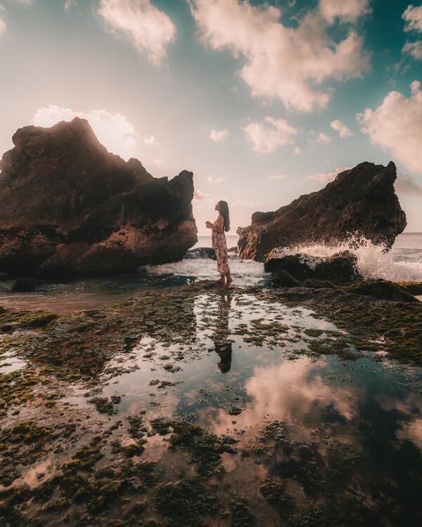 foto de uma mulher na água no meio de duas pedras
