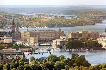 Vista de cidade com prédios e água ao fundo  Descrição gerada automaticamente