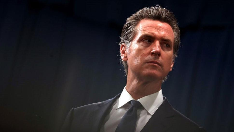 """SACRAMENTO, CALIFORNIA - AUGUST 16: California Gov. Gavin Newsom looks on during a news conference with California attorney General Xavier Becerra at the California State Capitol on August 16, 2019 in Sacramento, California. California attorney genera Xavier Becerra and California Gov. Gavin Newsom announced that the State of California is suing the Trump administration challenging the legality of a new """"public charge"""" rule that would make it difficult for immigrants to obtain green cards who receive public assistance like food stamps and Medicaid. (Photo by"""