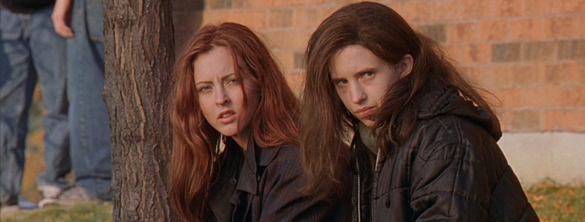 From left, Katherine Isabelle and Emily Perkins in Ginger Snaps, sitting outside their school. Courtesy of Lionsgate Films.