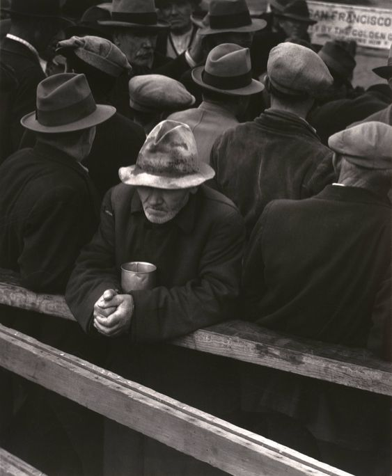 A photo of a man stood in the White Angel Breadline, 1933, by Dorothea Lange