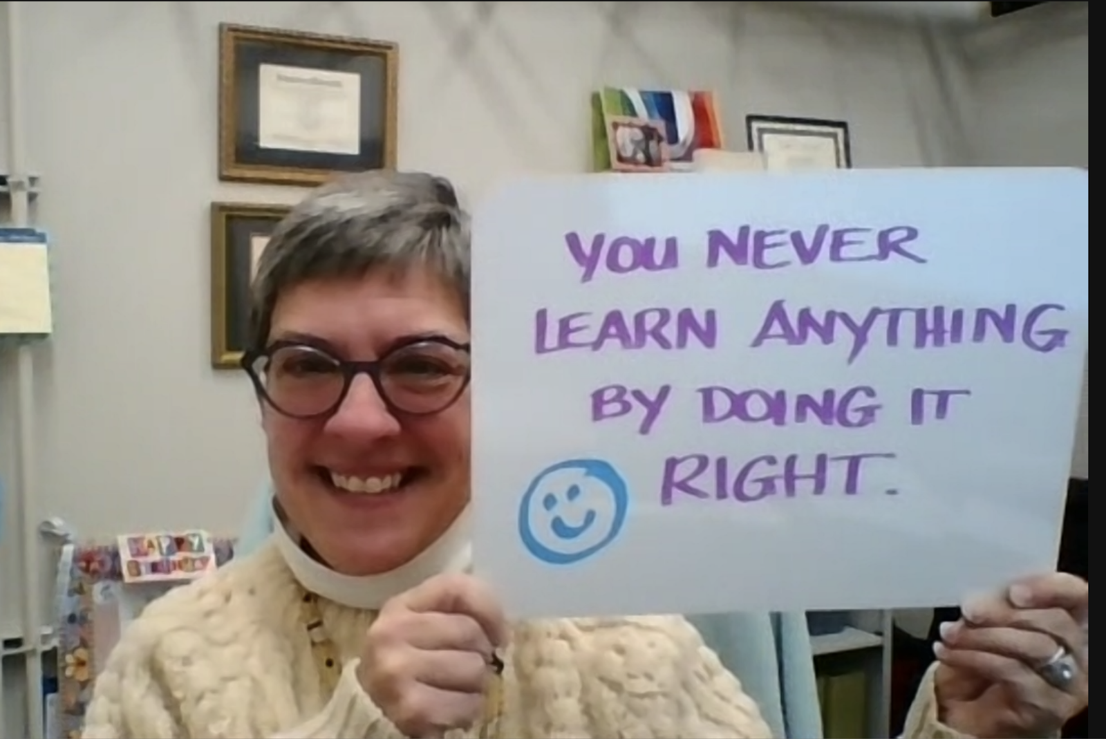 "Melissa Harrison, smiling and holding a sign that says, ""You never learn anything by doing it right."""