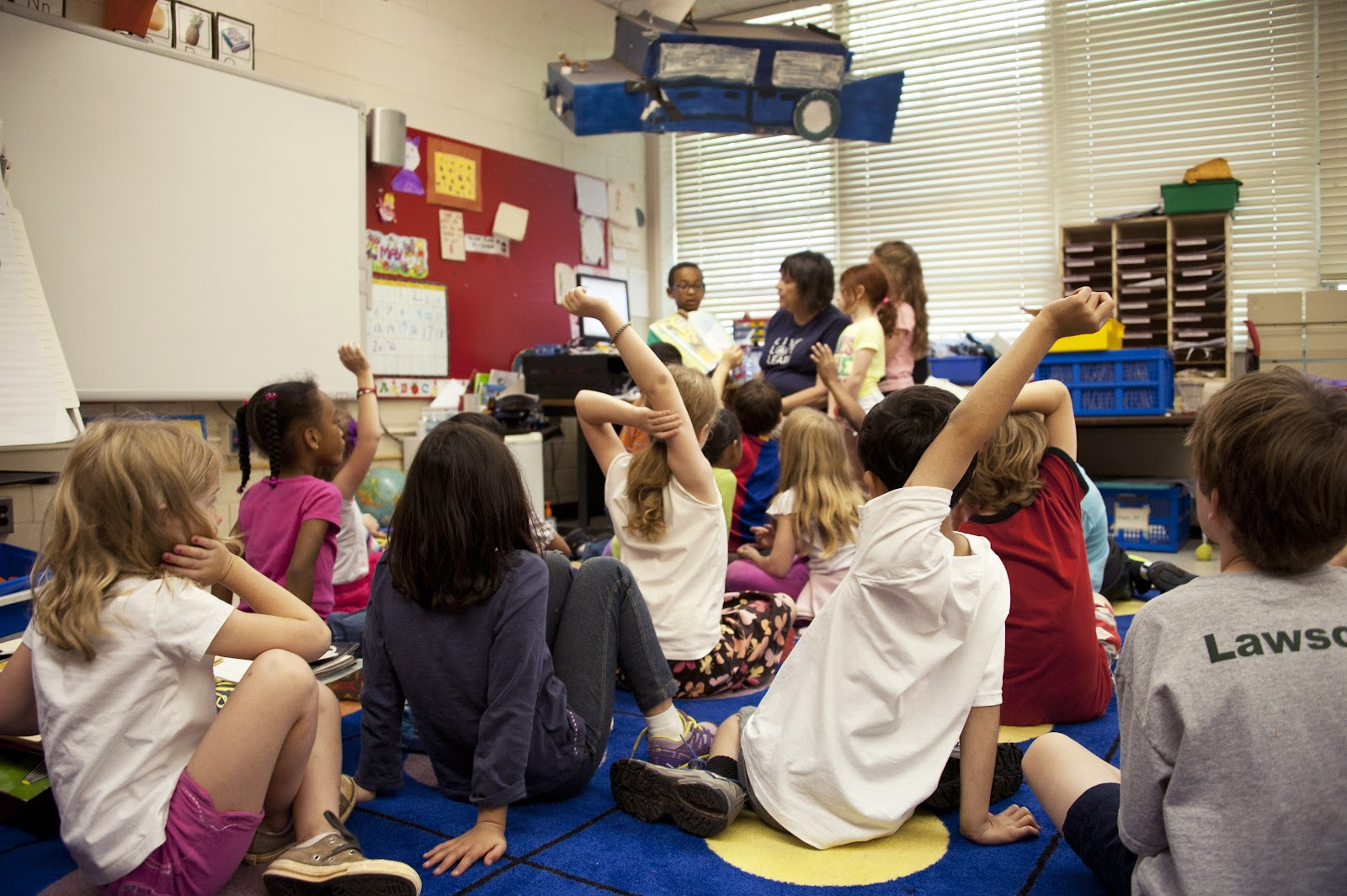 Elementary age students gather on a carpet, some with hands raised as their teacher sits in front of them all.