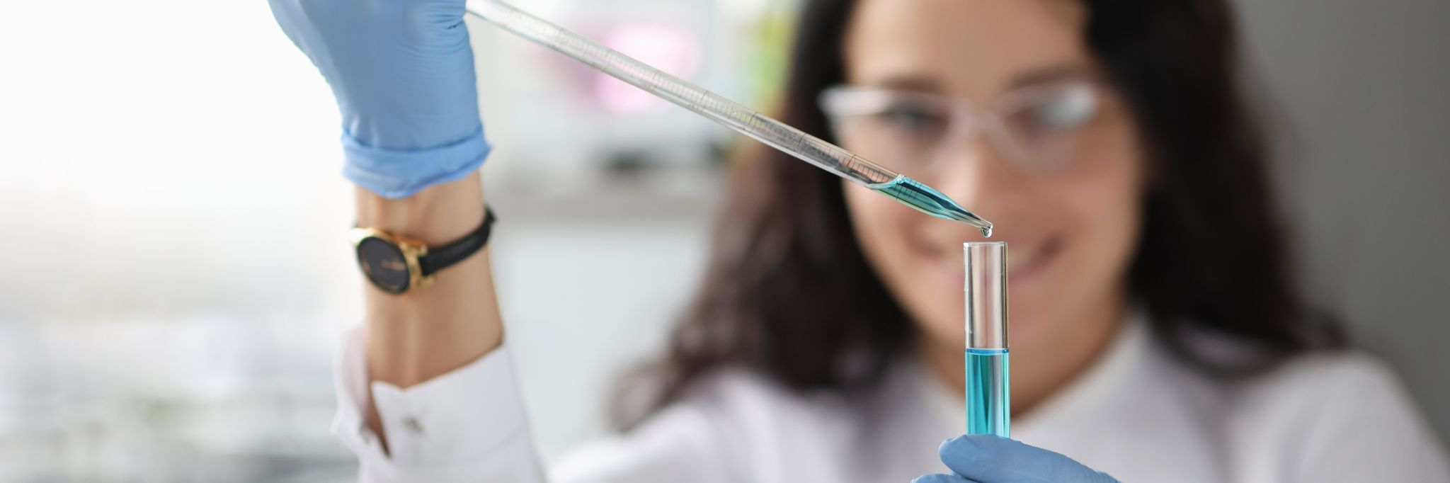 woman in a lab wearing safety gear uses pipette to measure liquid