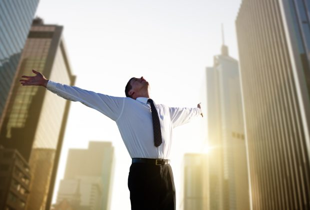 Image of a man with arms open celebrating - represents a schoolteacher celebrating after making a million dollars