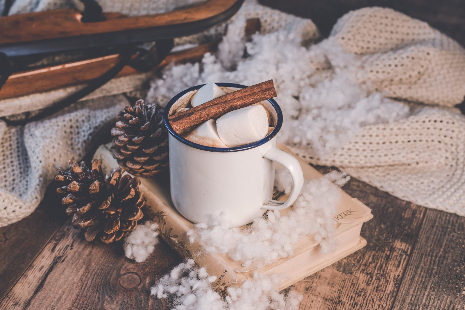 White Ceramic Mug with marshmallows and a cinnamon stick inside.