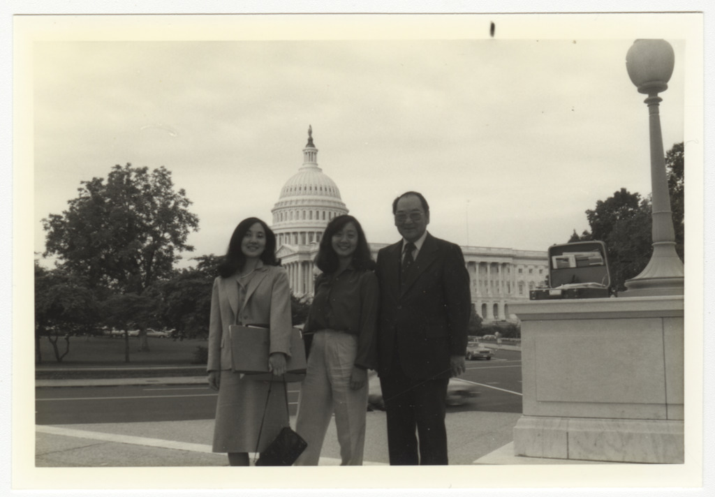 Members of the CWRIC committee, two women and a man, standing in front of the Capitol building in Washington, D.C.