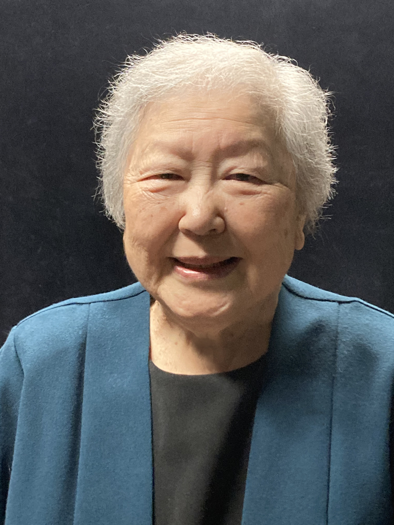 """Yoshiye """"Yo"""" Yasuda, who was recently interviewed for Densho's oral history program. She is smiling and wearing a blue jacket over a black shirt."""