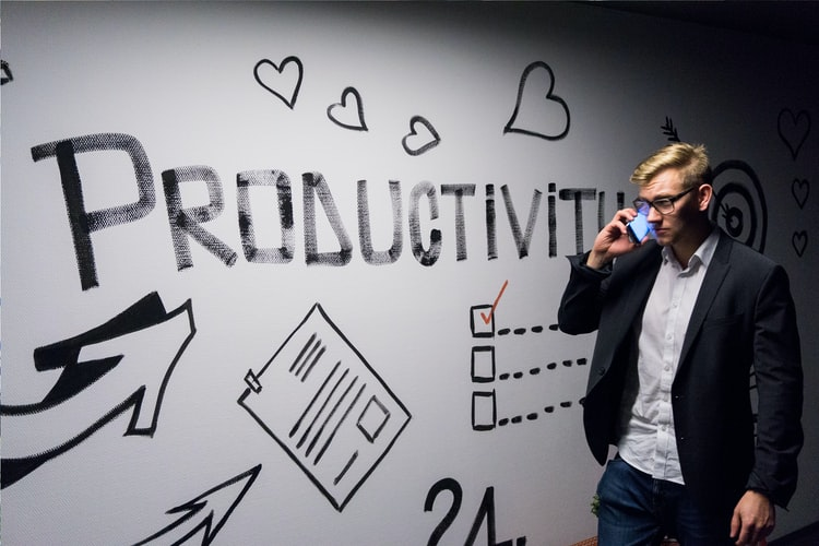 man on the phone standing next to wall art that says 'productivity'.