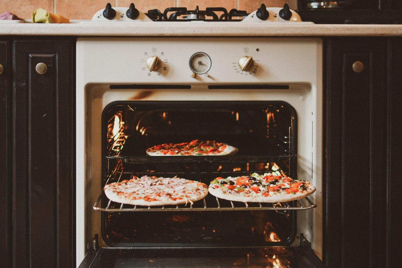 A pizza sitting on top of a stove top oven  Description automatically generated