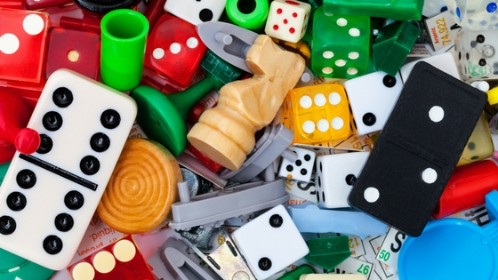 collection of dice and game pieces in a collage