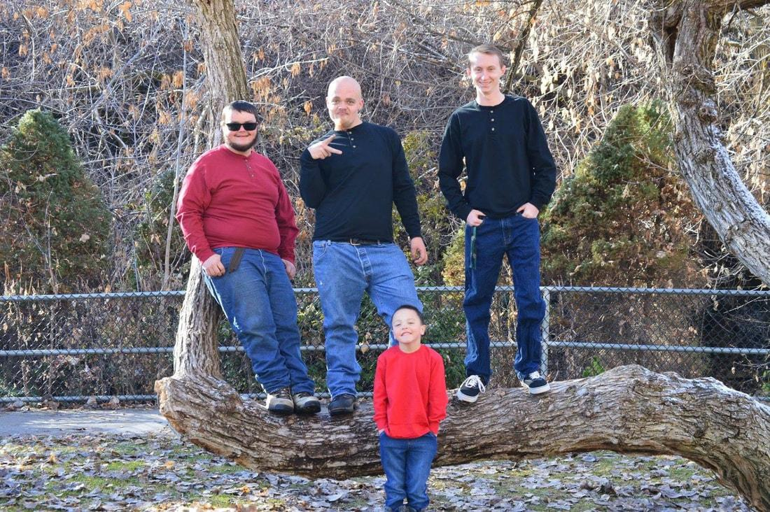 A group of people standing on a log in front of a waterfall  Description automatically generated with low confidence