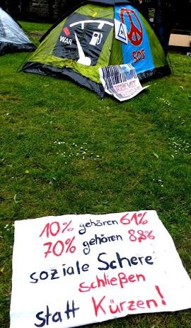 Zelt mit Friedensbemalung. Transparent im Gras: »10% gehören 61%, 70% gehören 8,8%, Soziale Schere schließen statt kürzen!«.