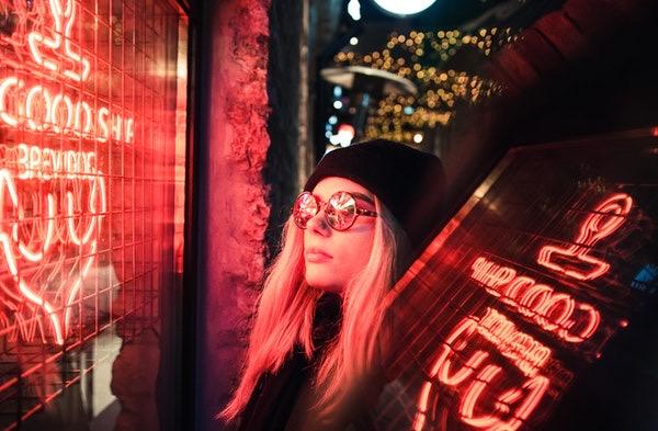 Foto de uma mulher com óculos olhando para uma vidraça com cores e palavras em neon.