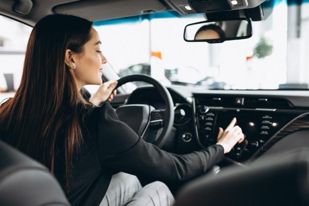 Mulher mexendo no rádio de seu carro com a mão direita, enquanto coloca a mão esquerda no volante.