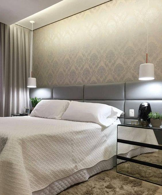Quarto de casal clean com cabeceira estofada na cor cinza, papel de parede cinza na parede de fundo, luminárias pendentes branca, criado mudo espelhada