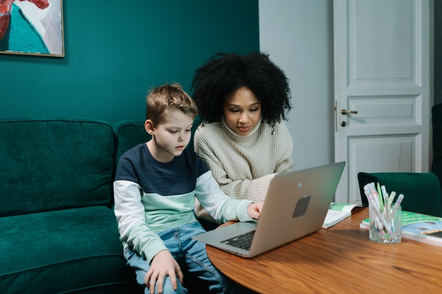 An adult and a child with a laptop.