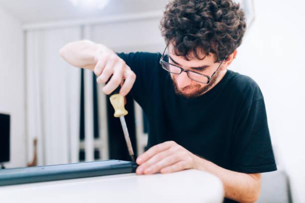 young man repairing laptop - broken laptop stock pictures, royalty-free photos & images