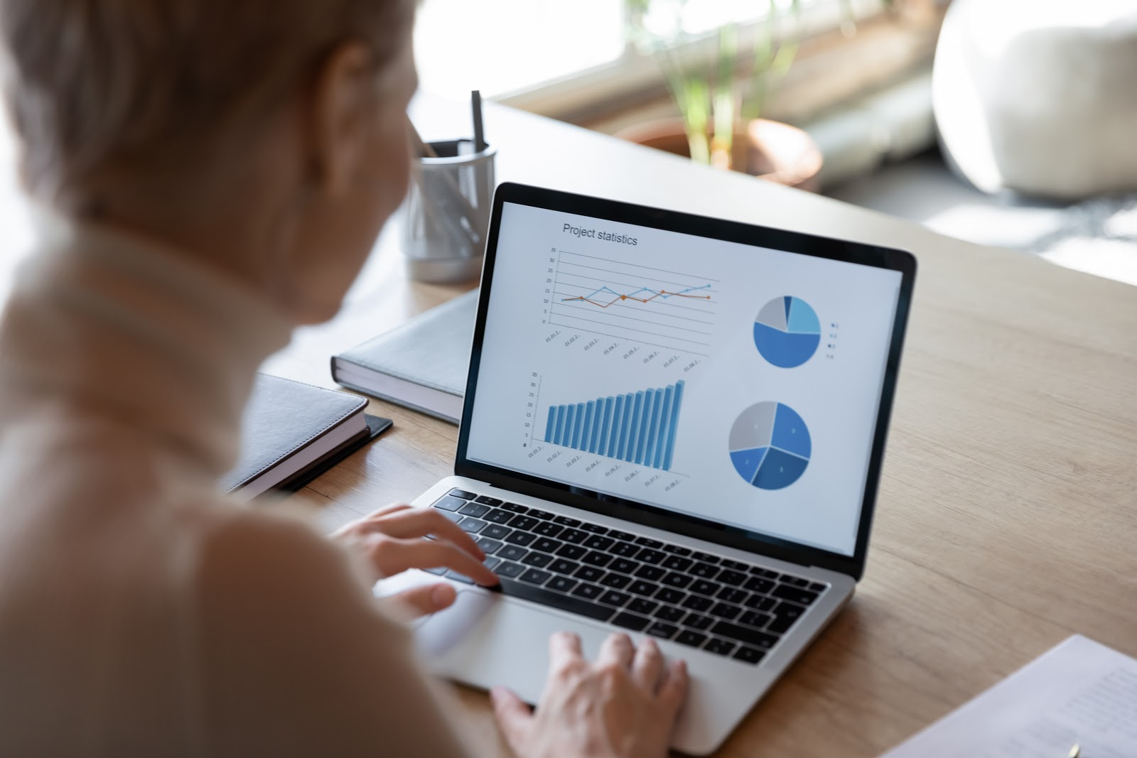 dividend tracker: Woman analyzing graphs on her laptop