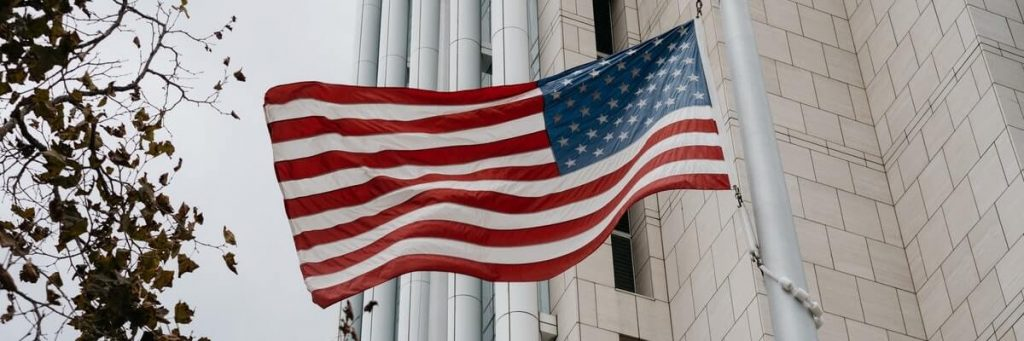 united states flag hanging from government building